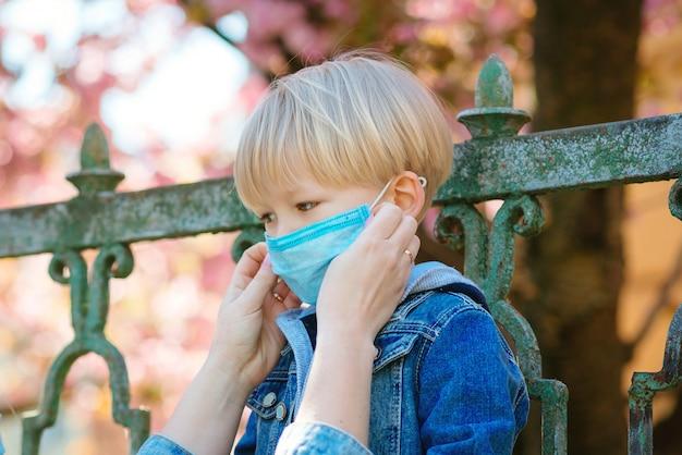 Мать надевает на ребенка стерильную медицинскую маску. ребенок, носящий маску, защищает от заражения вирусом, пандемии, вспышки и эпидемии болезней на карантине.