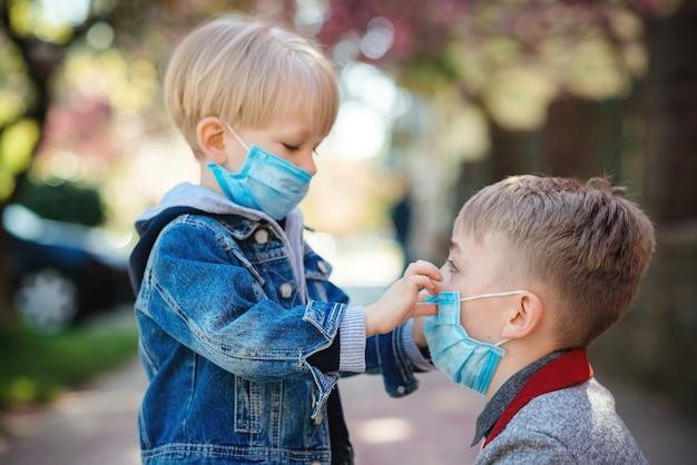予防コロナウイルス。散歩中に安全マスクの子供たち。コロナウイルスアウトブレイク。