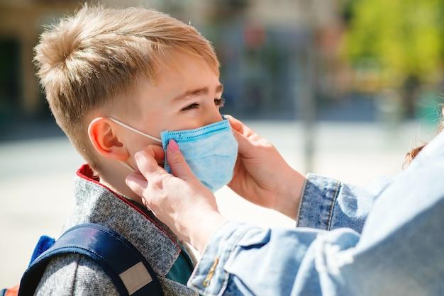 母は息子の顔に安全マスクをつけます。コロナウイルスを防ぐための医療用マスク。コロナウイルス検疫