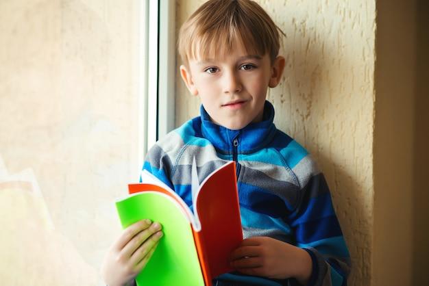 窓の近くの本を持つ少年。学校に戻る。