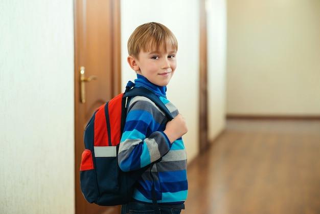 Счастливый школьник с рюкзаком собирается в класс. обратно в школу. ученик идет учиться с рюкзаком.