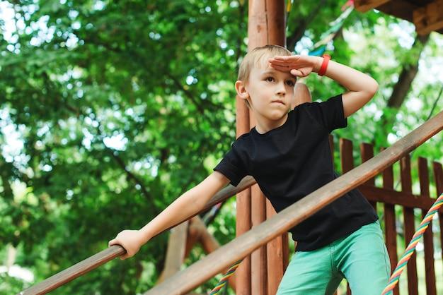木の家で遊ぶかわいい子供。夏の公園で楽しんで幸せな少年。