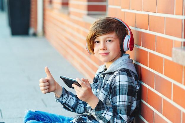 ワイヤレスヘッドフォンでかわいい少年は学校の休憩時間に音楽を聴く