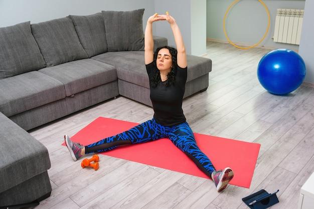 Молодая женщина делает упражнения на коврик для йоги. девушка с помощью планшета смотрит онлайн мастер класс. тренировка на дому.