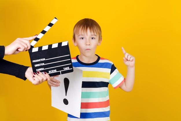 Продюсер снимает фильм. мальчик держит лист бумаги бумаги с восклицательным знаком. вдумчивый ребенок над желтой стеной. новая идея для школьного проекта.