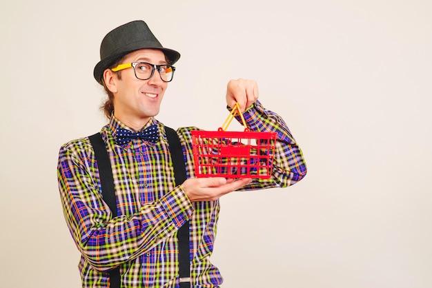 Парень ботаник держит пустую корзину для покупок. покупки онлайн. ботаник в очках готов к покупкам.