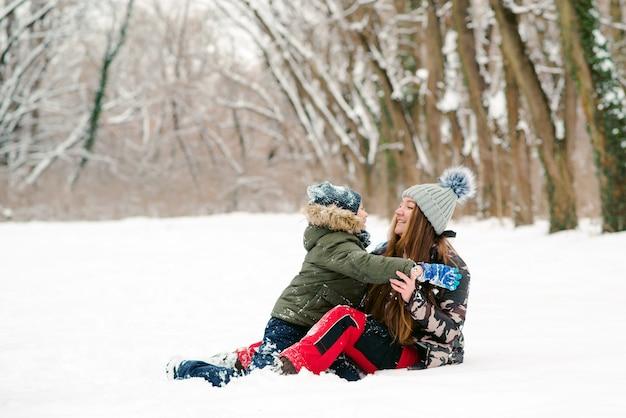 Молодая мать и сын с удовольствием в зимнем парке