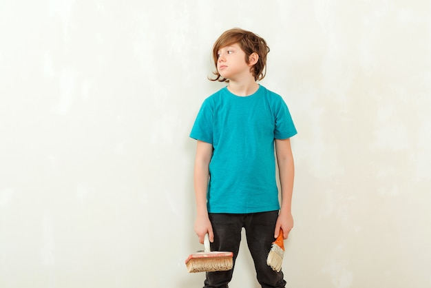 Парень готов покрасить стену в своей комнате. счастливый мальчик, холдинг кисти. сын помогает родителям красить стены. новый дом для семьи.