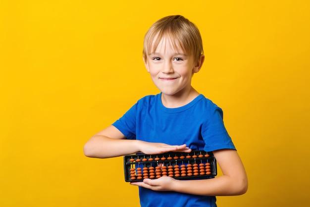 暗算を学ぶためのそろばんを持ってかわいい男の子