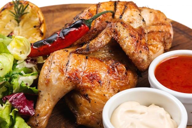 新鮮なサラダの葉を木の板に焼き鶏もも肉。