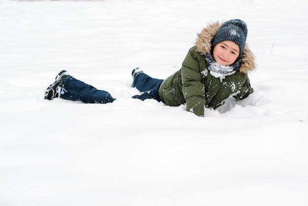 Счастливый мальчик лежит в снегу в зимнем парке