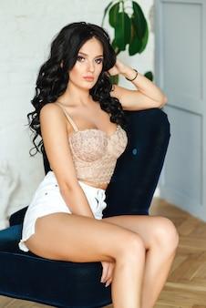 Соблазнительная молодая женщина позирует в студии. роскошный модный макияж и прическа. девушка в сексуальном корсете и шортах