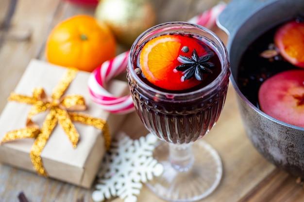 Глинтвейн в красивом бокале рядом с кастрюлей. горячий напиток в стакане. рождественская концепция семейный вечер с горячим напитком.