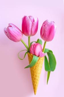 マカロンとピンクのチューリップの花束。アイスクリームのワッフルグラスのチューリップ。春の組成物。お菓子と花瓶のチューリップ。