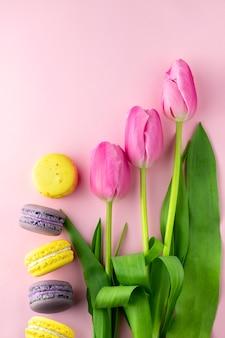 ピンクの背景のチューリップ、コピーライティングの場所。春のコンセプトです。チューリップのグリーティングカード。ピンクの背景の花と色とりどりのマカロン。夏のコンセプトです。春の背景