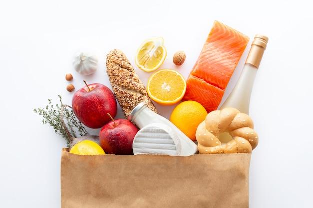 様々な健康食品の完全な紙袋。健康食品の背景。紙袋の果物と野菜の健康食品。栄養。ショッピング食品スーパーマーケットのコンセプト。ワイン、チーズ、フルーツ。ショッピング