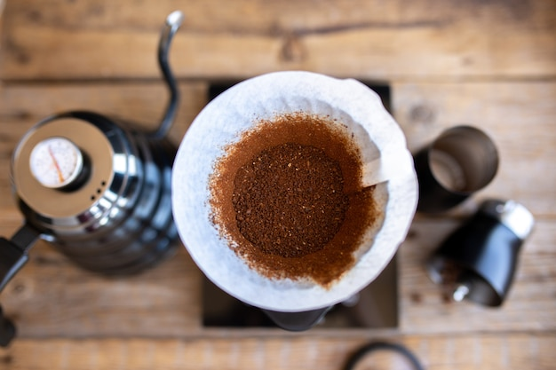 Молотый кофе в зернах в воронке. ритуал приготовления кофе. приготовление кофе в домашних условиях. отфильтрованный кофе, или перелив, является методом, который включает в себя наливание воды на жареные