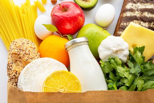 健康食品のフルペーパーバッグ。健康食品の背景。スーパーマーケットの食品のコンセプト。牛乳、チーズ、パン、果物、野菜、アボカド、パイナップル、スパゲッティ。スーパーで買い物。宅配