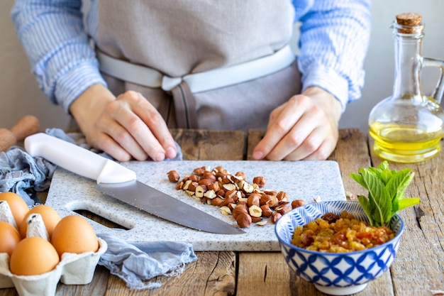 Измельчает фундук. повар измельчает орех на доске с помощью ножа.
