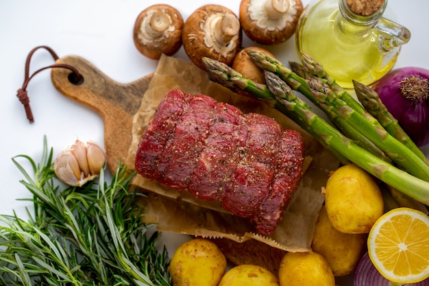 緑のローズマリーと木製のまな板で新鮮野菜と赤牛の生肉