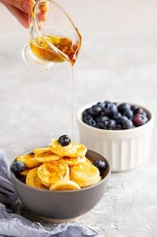 ミルクとミニのパンケーキ。ボウルにイチゴとブルーベリーと揚げたミニパンケーキ。メープルシロップの上面とミニのパンケーキ。