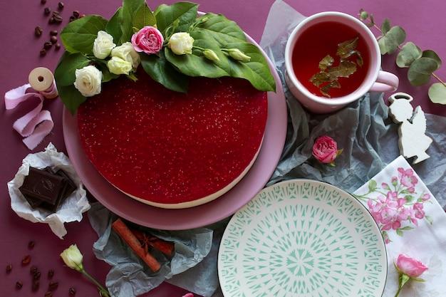 緑茶とラズベリーのチーズケーキ。ケーキは新鮮な花で飾られています。お茶と夏のケーキ。チーズケーキ