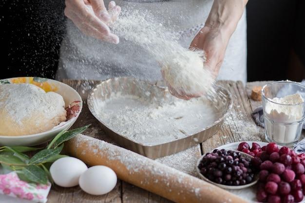 小麦粉が崩れる。パン屋は生地に小麦粉を振りかけます。