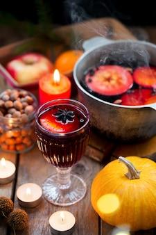 クリスマス赤ワインは、素朴な木製のテーブルの上のスパイスとフルーツのホットワインです。クリスマスの伝統的な温かい飲み物。柑橘系の果物、リンゴ、スパイスを鍋に入れたホットワイン。温かい飲み物