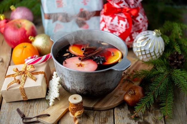 Рождество красное вино глинтвейн с пряностями и фруктами на деревянном столе. зимняя концепция. традиционный горячий напиток на рождество. глинтвейн с цитрусовыми, яблоками и специями на сковороде.