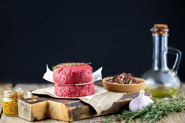 ハーブ、バター、調味料が入ったボード上の赤身の肉。ハンバーガーのビーフカツレツ。肉を調理します。生のハンバーガーカツレツを形成しました。豚のひき肉。木製のテーブルにひき肉。シェフズテーブル