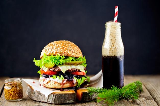 Свежий домашний бургер на небольшой деревянной разделочной доске на темном фоне. крупным планом дома сделал вкусный гамбургер на деревянном столе с бутылкой колы