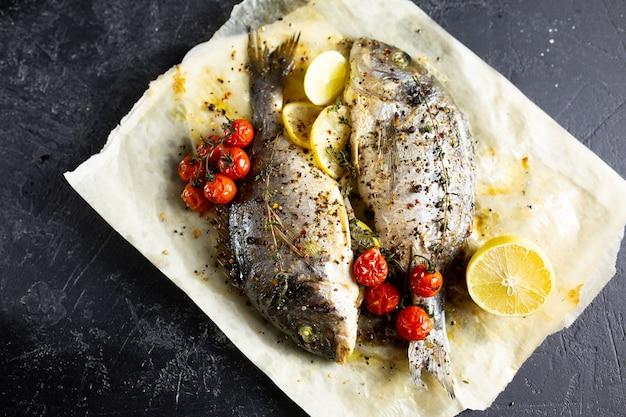 オーブンで魚を調理します。ドラドをオーブンで羊皮紙にチェリートマトとハーブで調理しています。