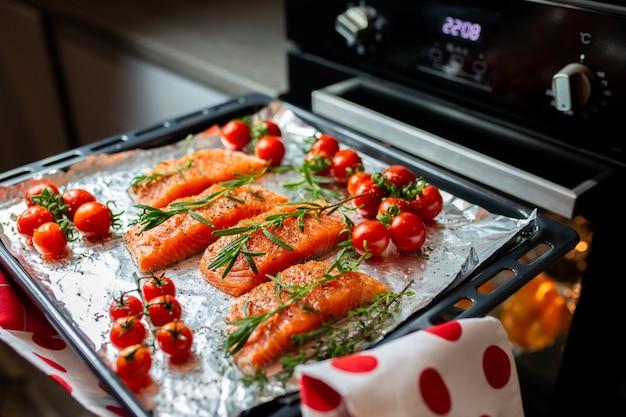 オーブンでサーモンを調理します。主婦が夕食を準備しています。シェフは赤い魚を調理しています。オーブンで魚を調理します。