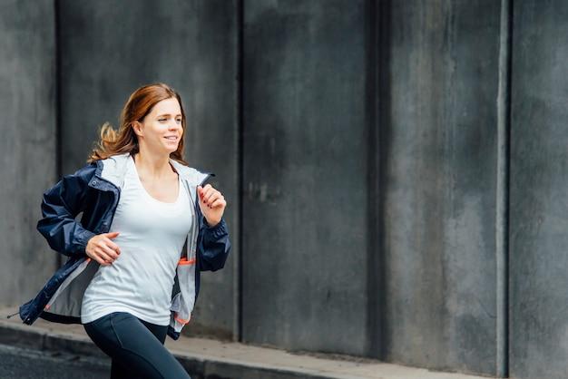 通りを走っている笑顔の若い女性の側面図。都会暮らし。