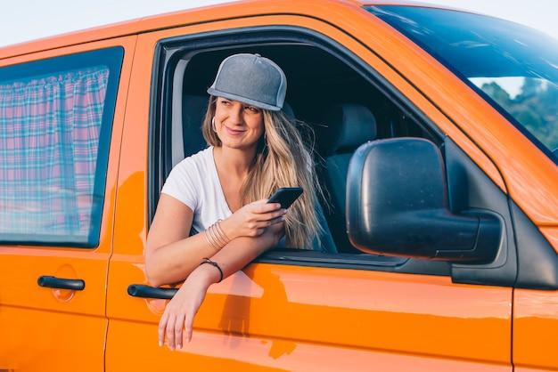 Красивая и привлекательная блондинка с кепкой в оранжевом фургоне с горами