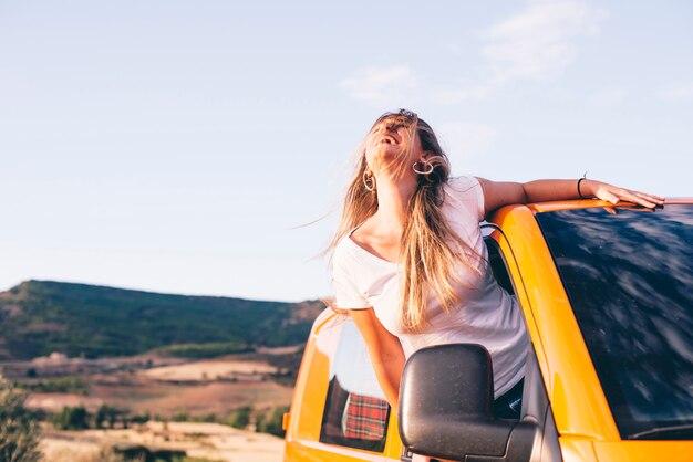 Девочка-подросток торчит из фургона в движении