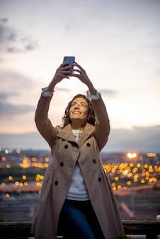 Довольно привлекательная и улыбающаяся женщина, используя смартфон в парке с партиями