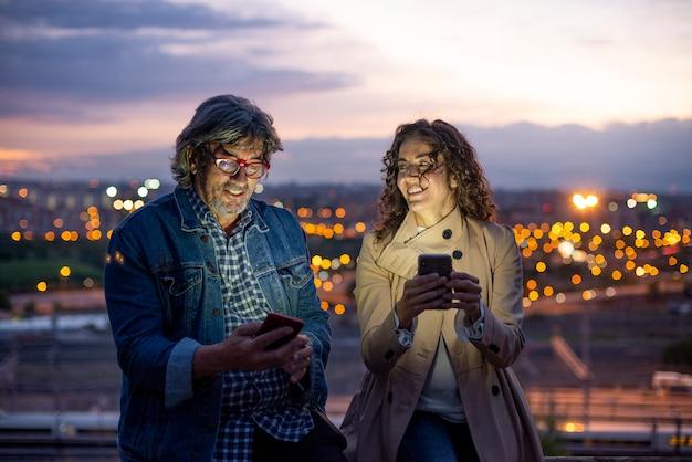 Улыбаясь привлекательная женщина и мужчина с помощью смарт-телефона
