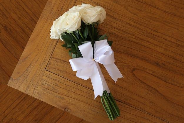 木製のテーブルの白いバラの花束