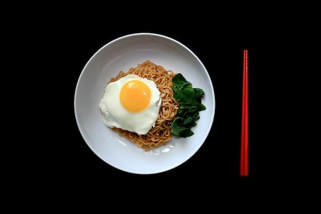 サニーサイドアップ卵と野菜のおいしい焼きそば。白い皿で提供しています