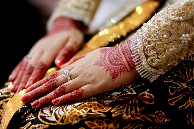ジャワの花嫁は、伝統的な美しいヘナ、ケバヤ、バティック、結婚指輪を使用しています。