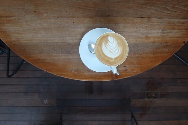 丸いテクスチャの背景にスプーンとプレートとラテアートコーヒーのカップ