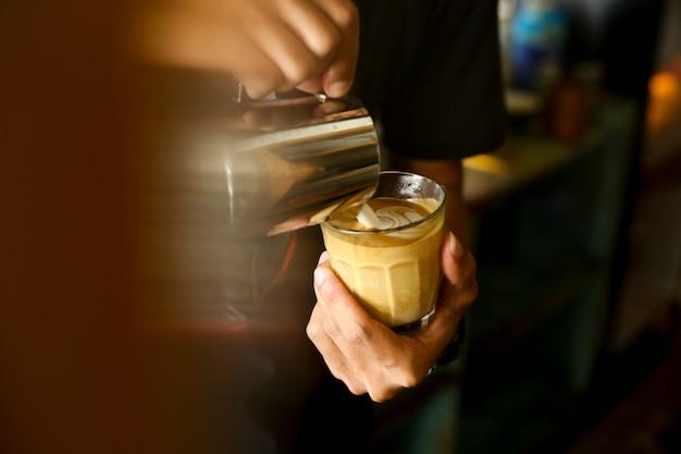 男性の手のクローズアップイメージバティスタ注ぐミルク、ラテアートの新鮮なカプチーノを作る