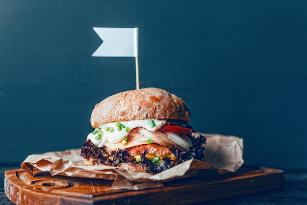 木製の背景に本物のハンバーガー。大きくてジューシーなカツレツの柔らかいチーズソースとマスタード。素朴な