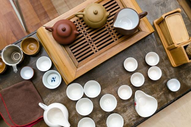 Китайская чайная церемония. стол с чайниками, мисками и чайной доской. вид сверху.