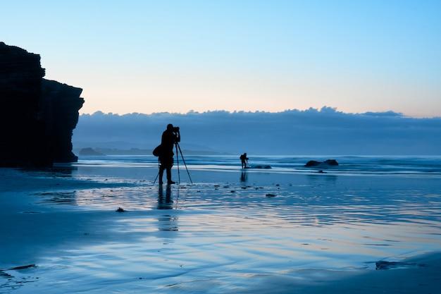 青の時間中にビーチで働く写真家