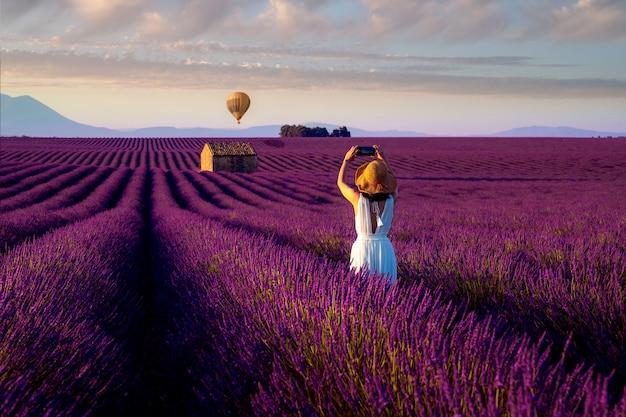 Азиатская девушка путешествия в сиреневом поле.