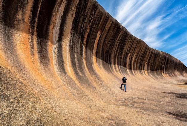 旅行者は波の岩を写真に撮る