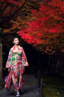 京都の古いお寺で伝統的な着物ドレスの日本人の女の子を歩く