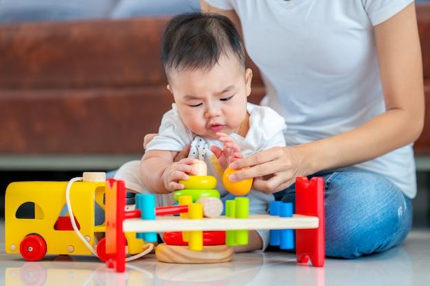 母は森のおもちゃで彼女の赤ちゃんと遊ぶ